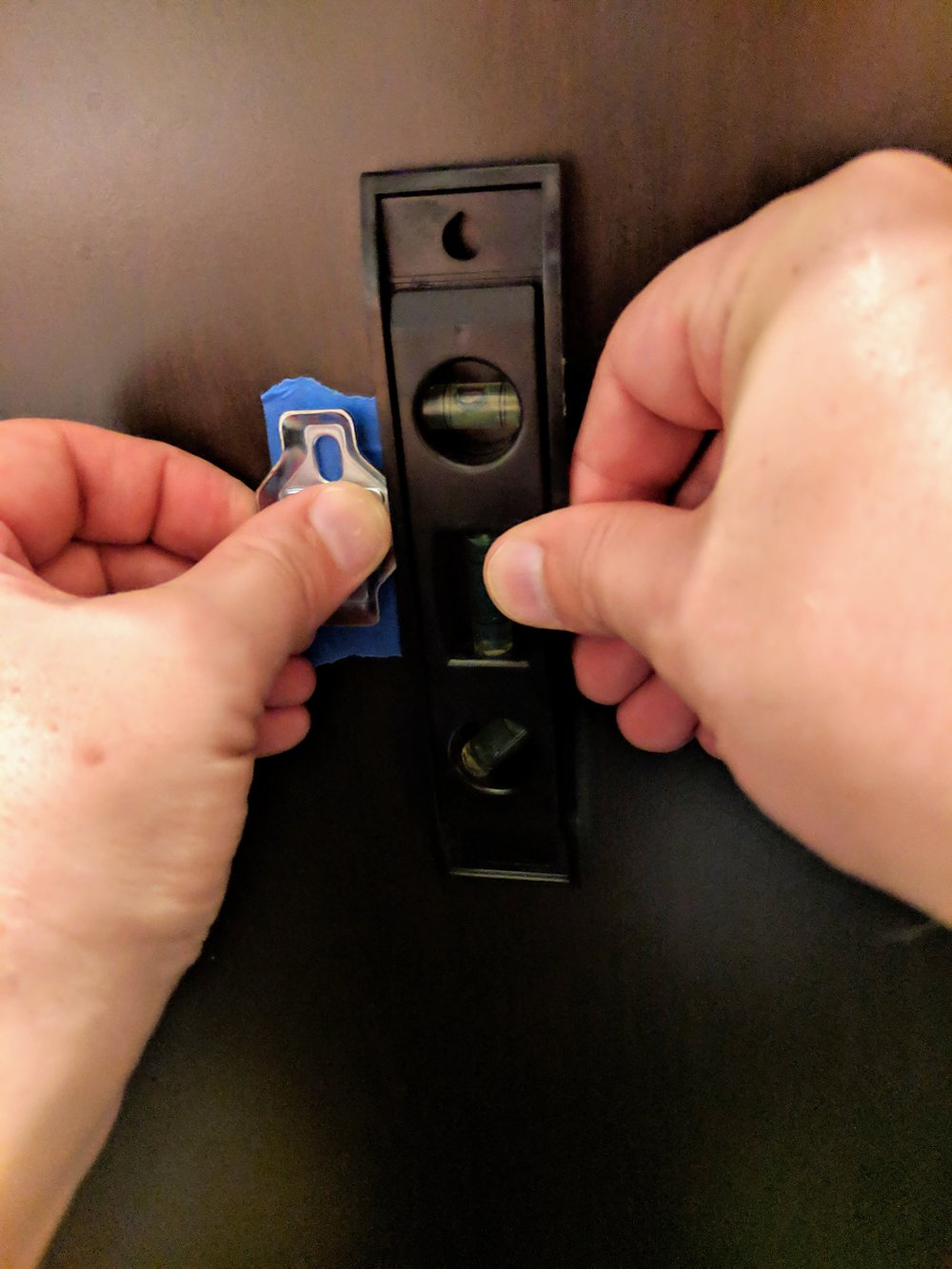 Used Painter's Tape to help mark our holes and protect the cabinet after leveling the bracket.
