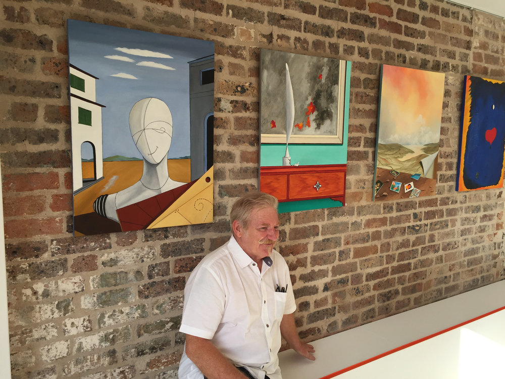 "Ivor Cole under his painting ""The Poet Smiles"" at Disorder Gallery"