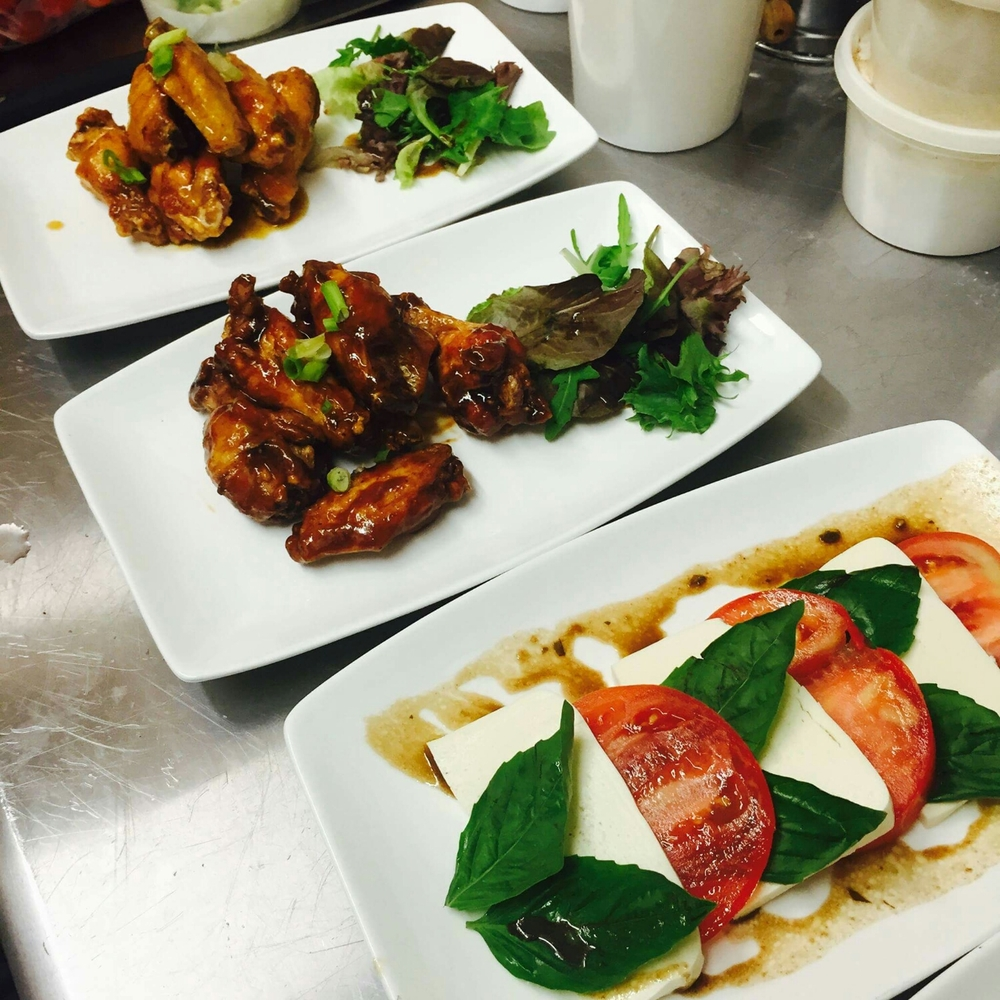 wing dishes and fresh mozzarella and tomatoes