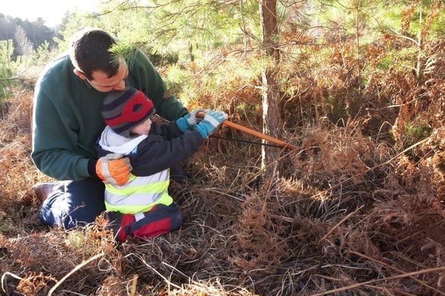 Man helping a child cut down a tree