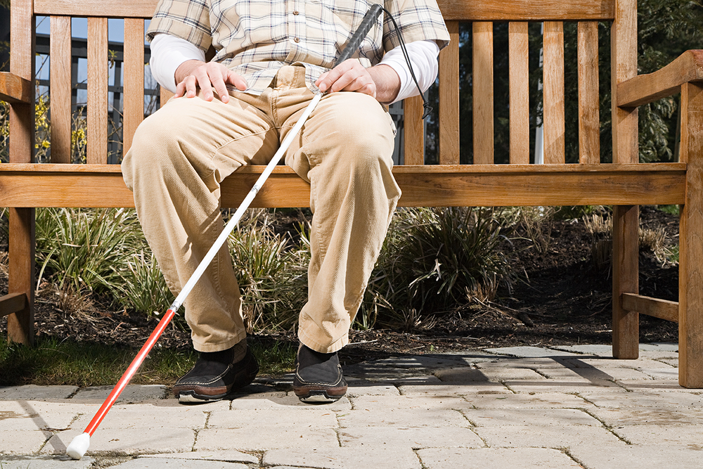 White Cane User Sitting on Park Bench