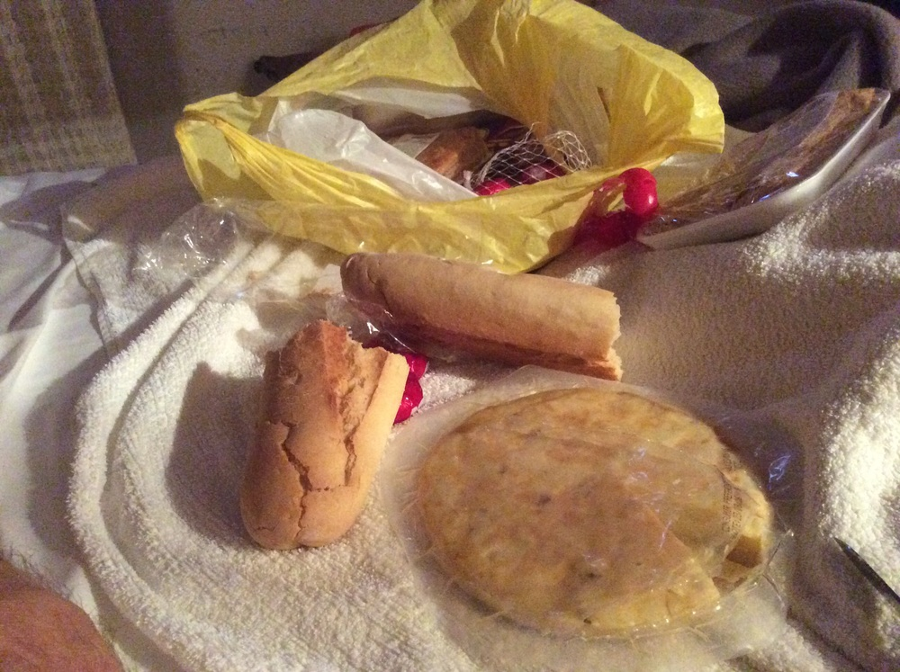 Dinner in my bed. it's 11:00pm. Note the round tortilla patata (cold potato omelette)