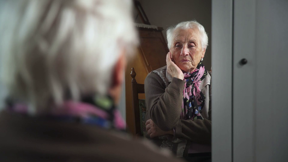 videoblocks-sad-and-depressed-old-woman-in-the-mirror-touches-hair_b2u7whejhx_thumbnail-full01.png