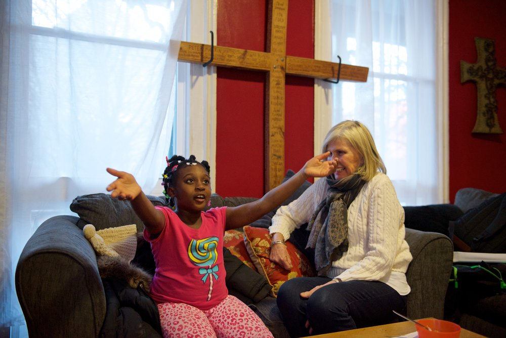 A young girl tells her mentor a story in an after school program at Hartford Catholic Workers.