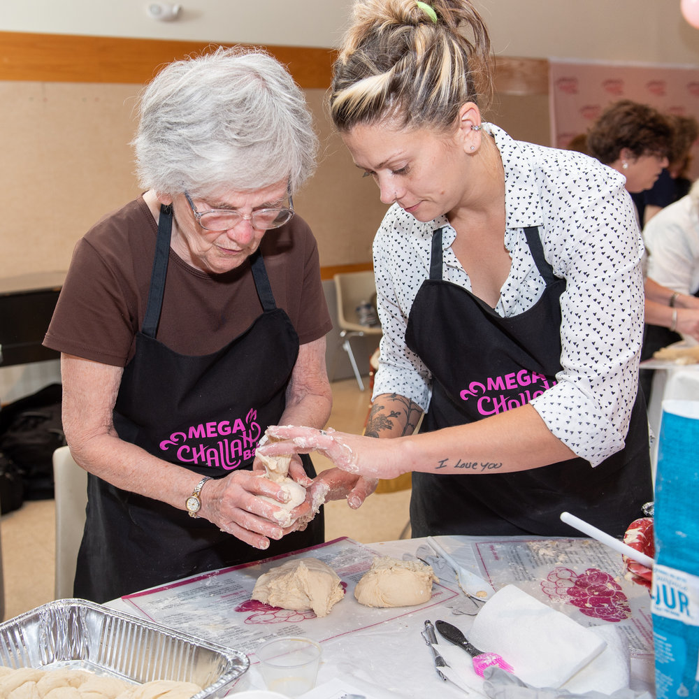 Rachel Morales (right), of East Longmeadow, MA, helps her 'bubbe' Bredine Pennington, of Springfield, as the two make Challah Wednesday night at the Mega Challah Bake sponsored by Chabad Women's Circle of Longmeadow. The 'I love you' tattoo caught my eye as I watched her tenderness with her 80-year-old grandmother, who converted to Judaism in her 40s after a long spiritual journey. The event drew 120 women to the Jewish Community Center, some who'd been baking challah all their lives, others who were trying it for the first time.