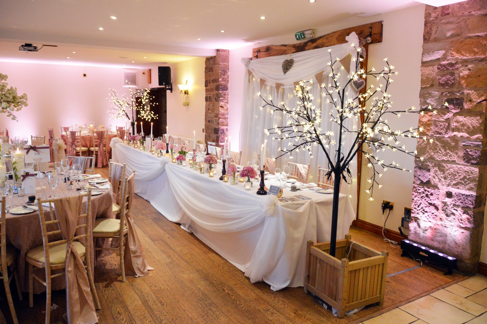 Fairy light trees next to the top table and top table drape