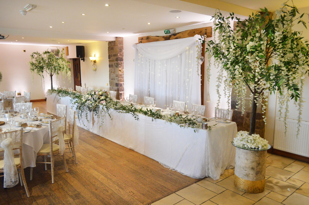 Wisteria trees next to the top table on logs