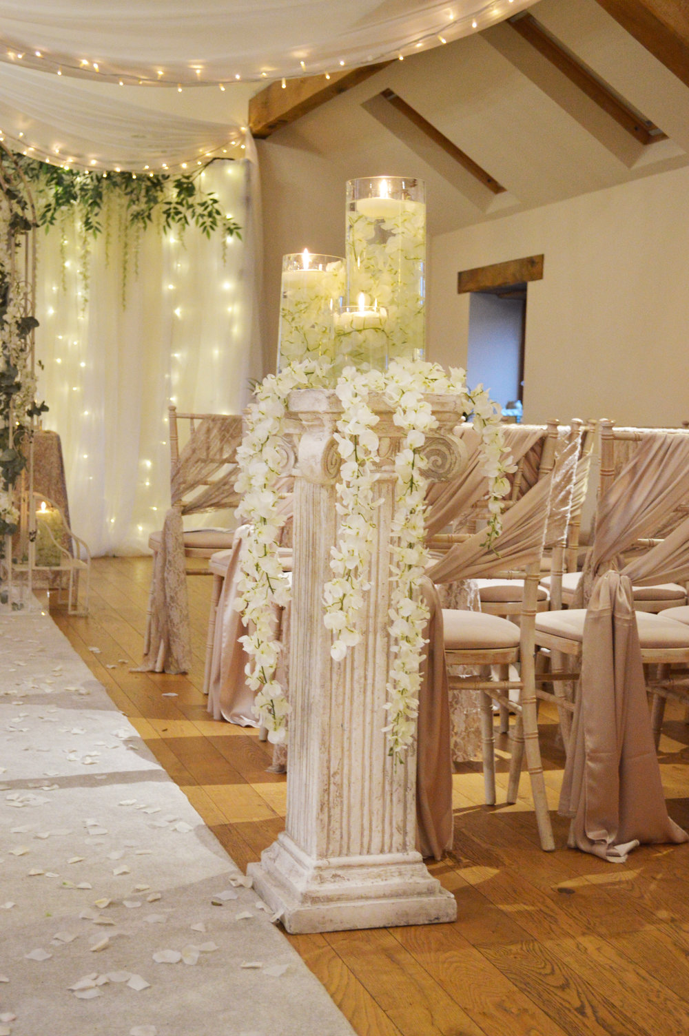 Pillars with floating candles and hanging flowers