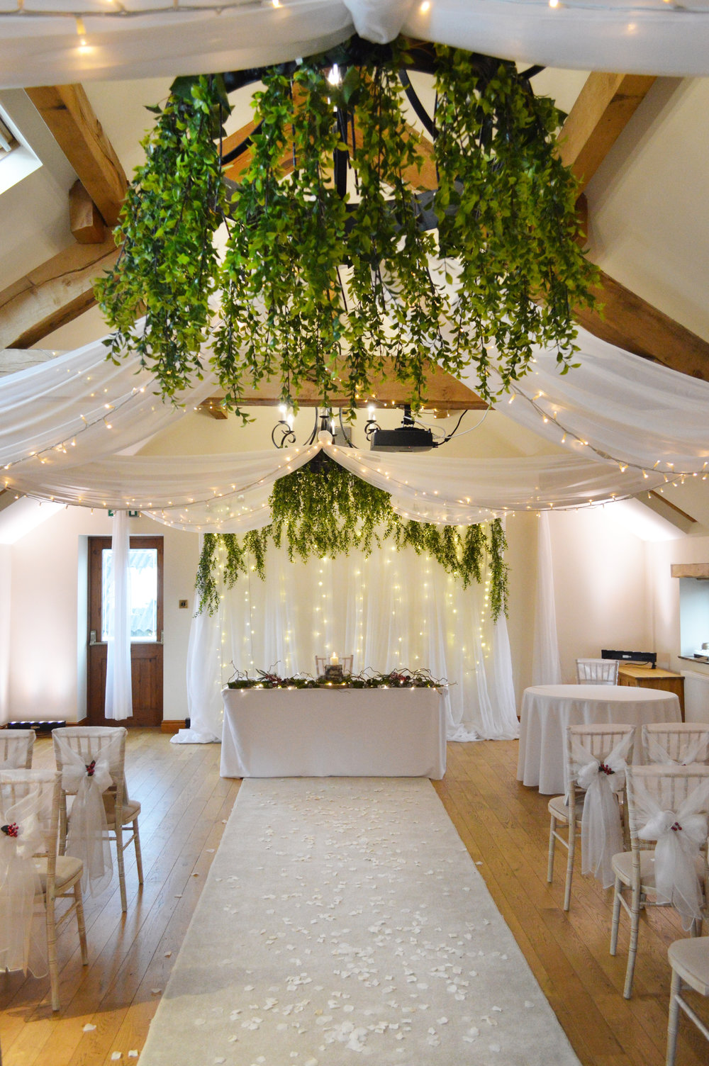 Greenery on chandeliers and fairy light backdrop