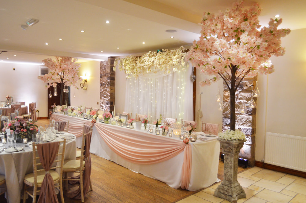 Pink blossom trees on pillars, hanging flowers on fairy light curtain and top table drape