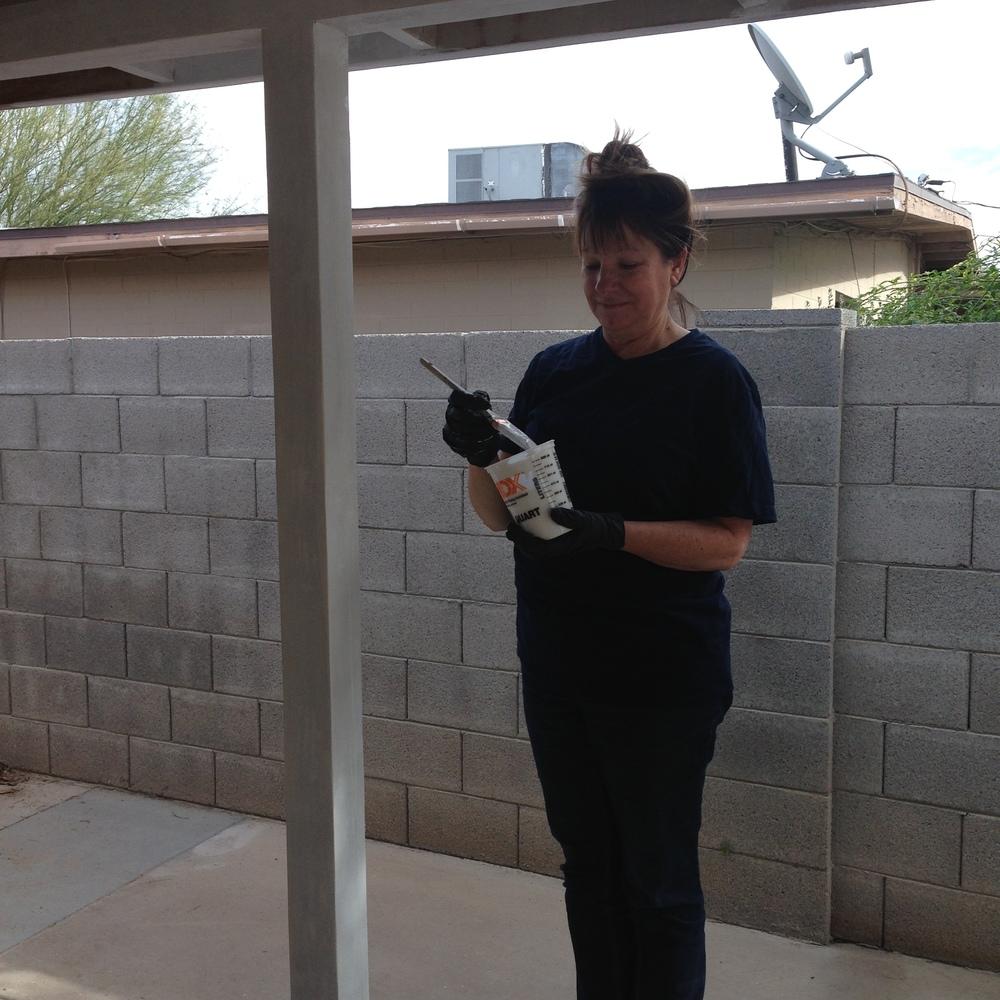 Mom spackling the backyard pillars.