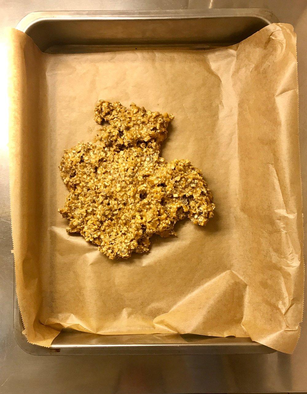 Erdnussbutter-Agavendicksaft-Haferflockenmischung in die Kuchenform streichen.