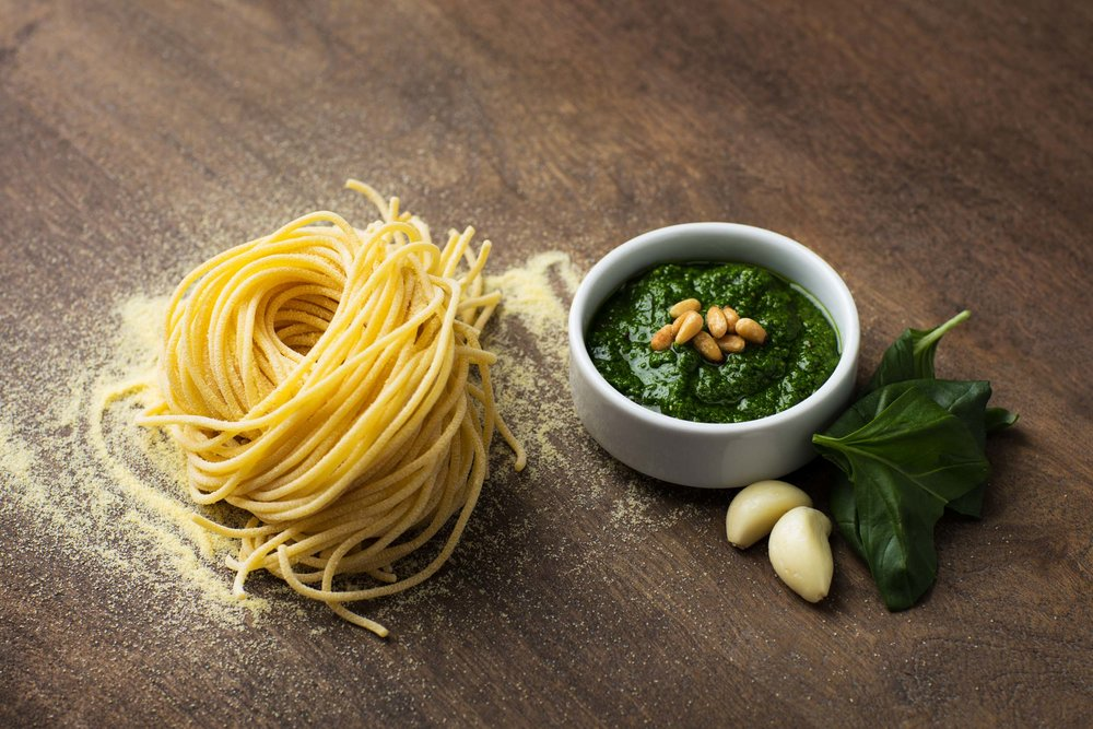 Handmade spaghetti pasta with basil pesto and garlic