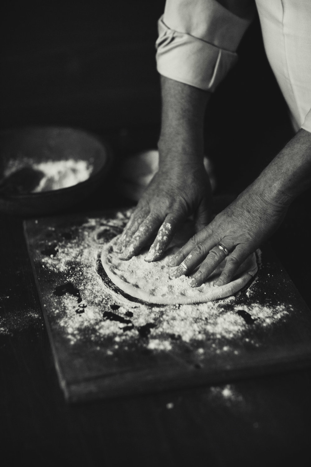 Hand tossed traditional pizza dough with flour