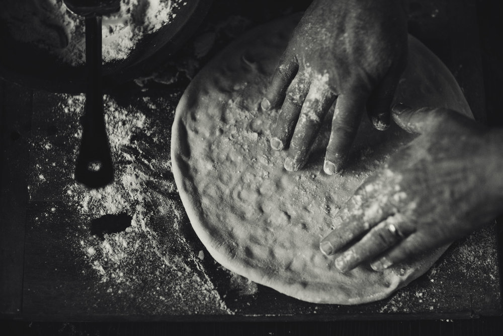 Hand tossed pizza dough flour covered hands