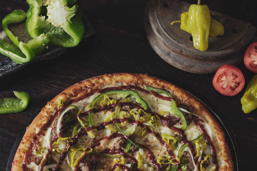 Fresh baked hand tossed pizza with green peppers, banana peppers, and barbecue drizzle