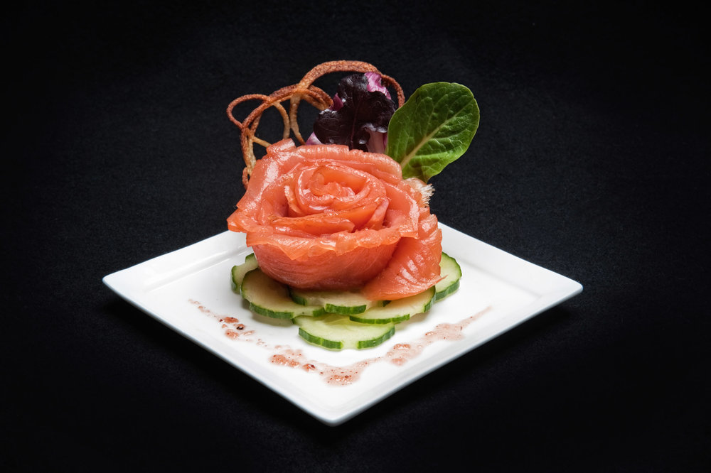 Rose made from salmon sitting on sliced cucumbers