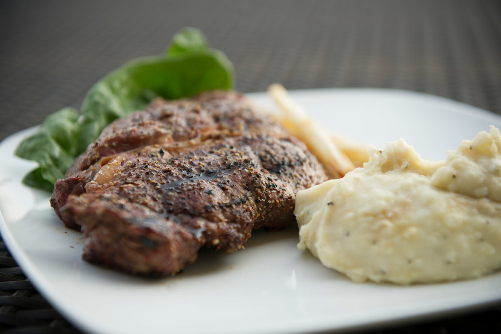 Roasted ribeye steak with whipped potatoes and spinach
