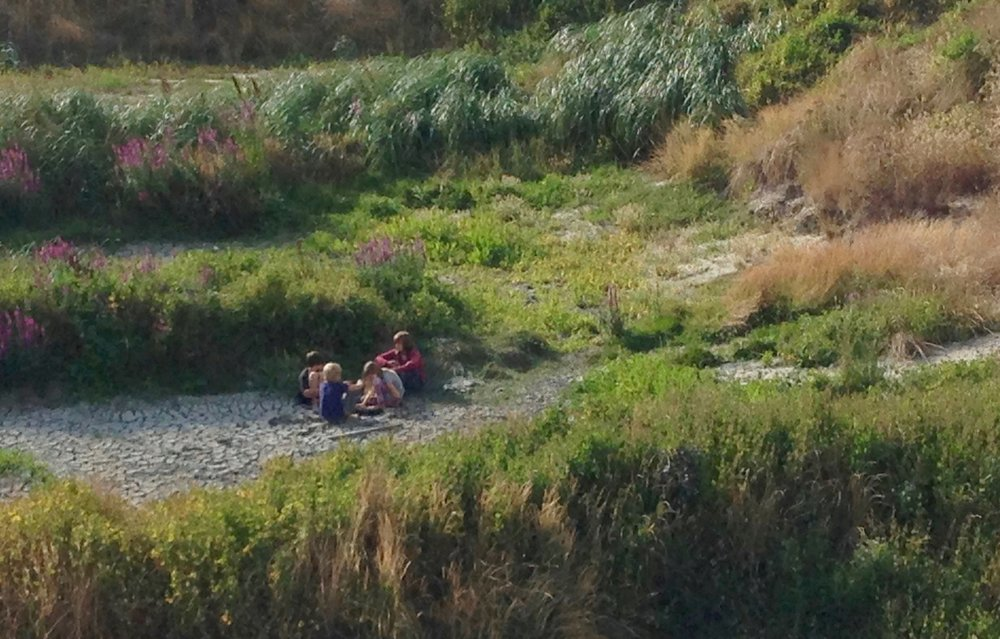 Boat kids enjoying their own world in a cool sandpit; Newport, OR.