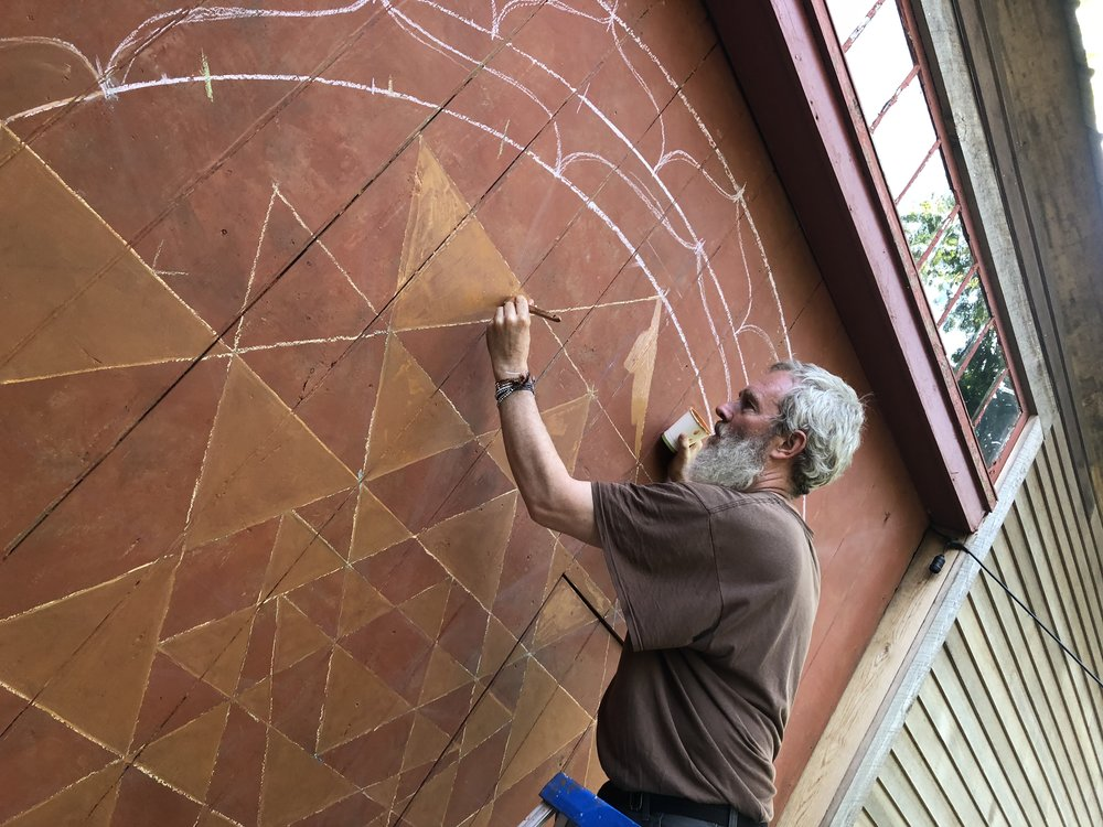 Sean creating a Mandala on the side of a wooden barn in New Hampshire