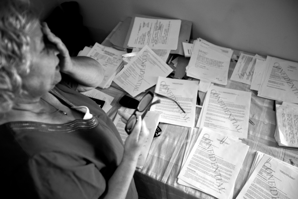 """Lynda organizes stacks of papers that show her legal guardianship over Paul as well as records documenting mental health treatment over the years. For the first time in a long time, Lynda couldn't afford to pay a private attorney. Paul's appointed attorney told Lynda he needed as much paperwork as he could get to document Paul's mental illness. """"I should not have to be doing this,"""" Lynda said."""