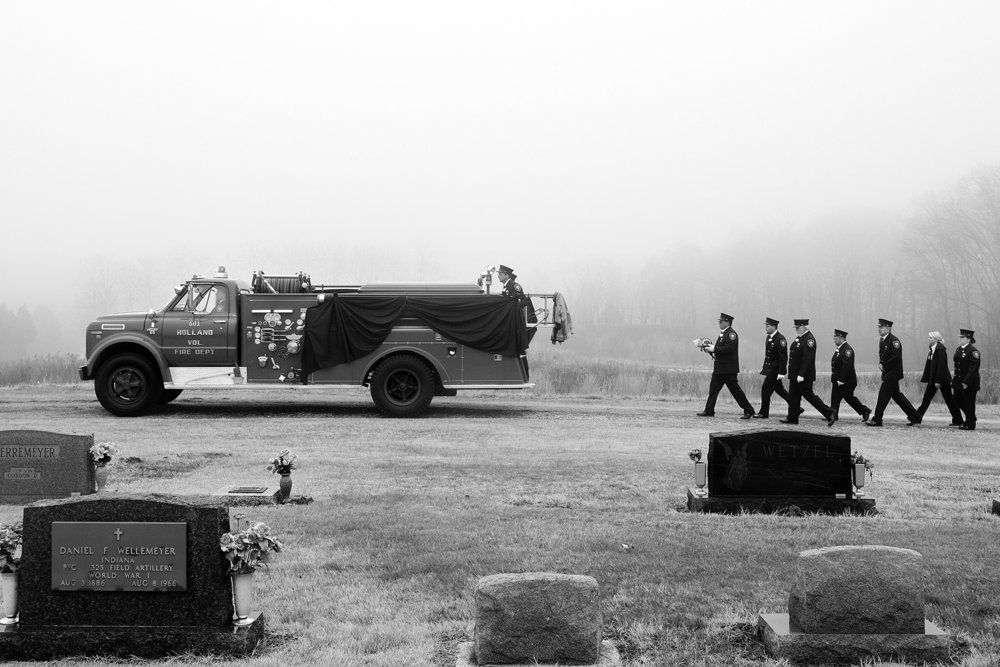 Members of the Holland Volunteer Fire Department walked behind a 1968 Chevrolet fire truck as it carried the casket of Doug Partenheimer, 54, of Holland, through the Holland United Methodist Church Cemetery. Partenheimer was a member of the town's fire department for 35 years, during which time he served as assistant fire chief and was most recently the acting treasurer. The old pumper was purchased new by the department in 1968 and is kept around to be used in parades. Holland Fire Chief Greg Englert said it was the first time to be used in a burial procession for a member of the department.
