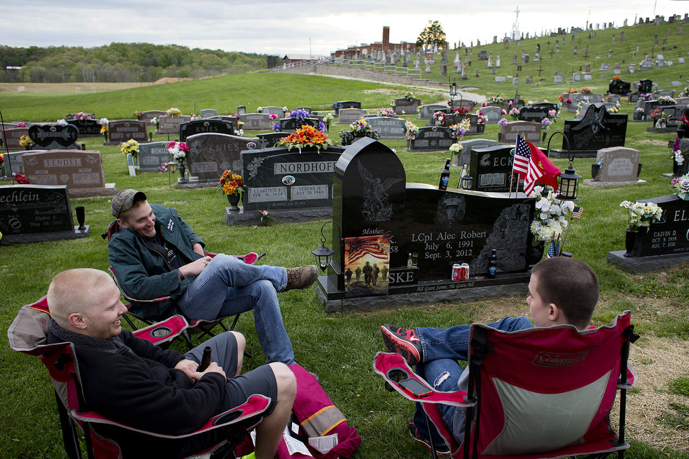 Tyler Lampert, left, and Logan Ingle, both of Dubois, and Logan Borden of Jasper sat near the gravesite of their high school friend, fallen Marine Lance Cpl. Alec Terwiske of Dubois, in St. Celestine Cemetery in Celestine. The three men said they and other friends will gather from time to time at Terwiske's gravesite, sit in lawn chairs and just spend time visiting their friend.