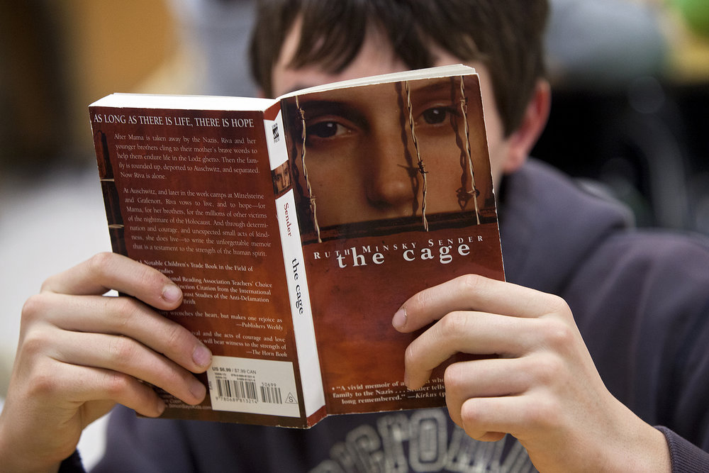 "Holy Family seventh-grader Adam Krempp joined a small group of his classmates in reading the book ""The Cage"" by author Ruth Minsky Sender during class. Alison Lindauer's class spent the class period beginning to read different books about the topic of the Holocaust in small groups. Each group will create a ""resource box"" that is decorated in accordance to the book they read and the box will be filled with items related to the book as well."