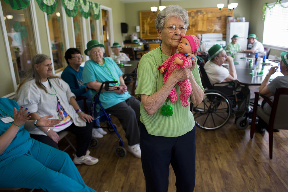 Cuddling with her baby doll, The Waters of Huntingburg resident Marge Short swayed side-to-side to the music during a St. Patrick's Day celebration for residents in the Hope Springs wing of the Huntingburg facility. Hope Springs is a unit with specialized care for residents with Alzheimer's and dementia. Short, who has dementia, has three dolls she enjoys caring for on a daily basis. Two of the dolls are her granddaughter's former dolls from more than 20 years ago.