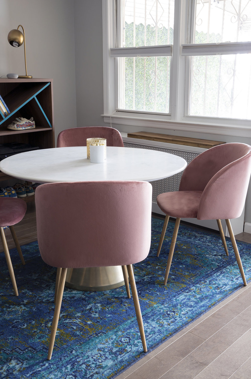 marble table pink chairs blue rug dining room decor.jpg