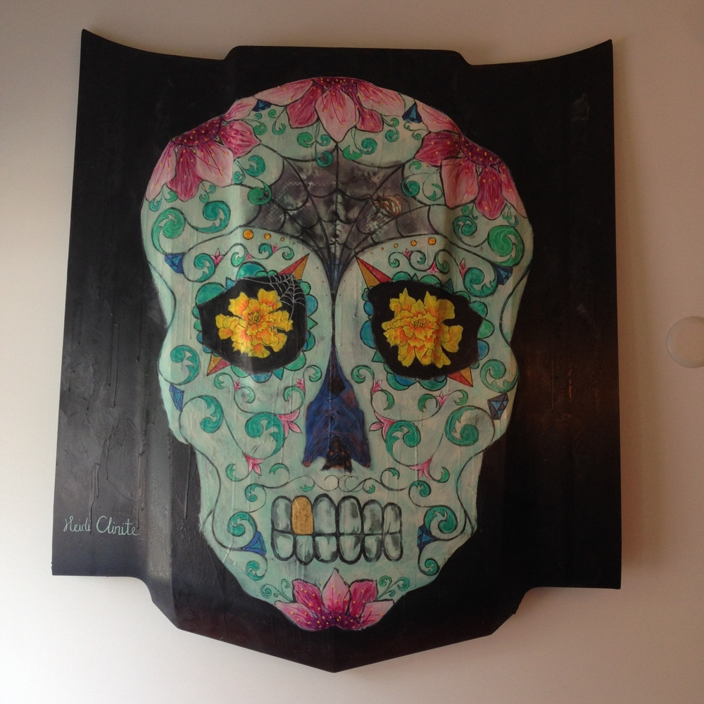 Sugar Skull on hood of car on display at El Camino Taqueria, Downtown Macon. Acrylic, spray paint & iridescent paint. Details to look for: lace pattern on background, Spanish rose on gold tooth, irridescent bat in nasal cavity, iridescent diamonds, spider in web, and then some. 2016.