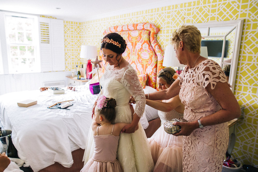 a flower girl hugs her mum, the bride. creative wedding photography north yorkshire teesside north east + stop motion wedding films uk