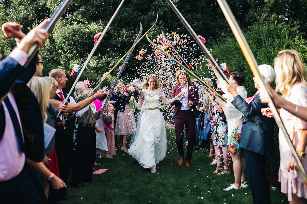 a couple walk through a guard of honour created with skis while guests throw confetti at them. colourful wedding at bentley wildfowl and motor musem near Lewes near Brighton. stop motion wedding