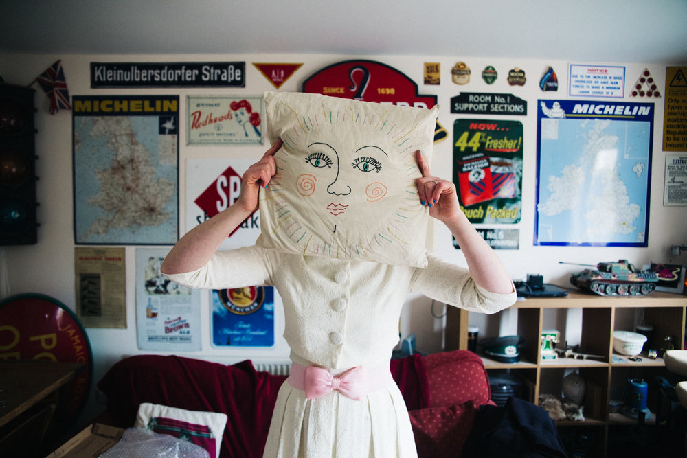 a bride holds a pillow with a face up to her head. london city centre wedding photographer. stop motion wedding films videos uk