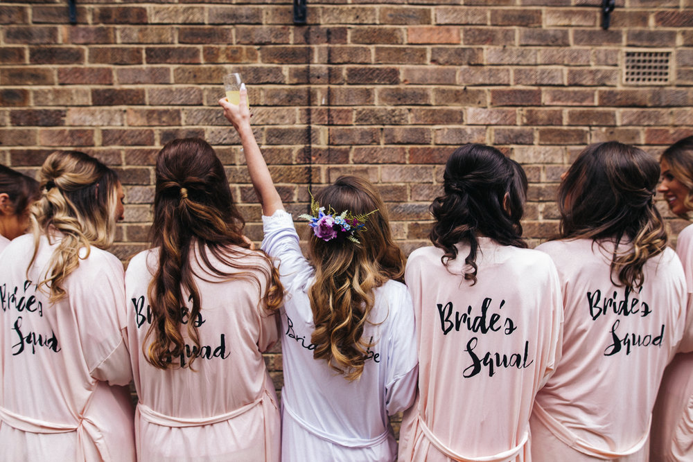 a bride and bridesmaids stand with their back to the camera in matching dressing gowns. worsall village hall wedding north yorkshire photographer. stop motion wedding films videos uk