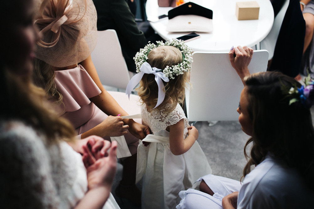 little girl, dressed for a wedding, having her bow tied up by bridesmaids. wedding at worsall village hall north yorkshire. stop motion wedding films videos uk