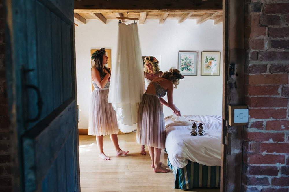 a bride and bridesmaids organise her wedding dress and accessories before getting dressed. hendall manor wedding. stop motion wedding films videos uk