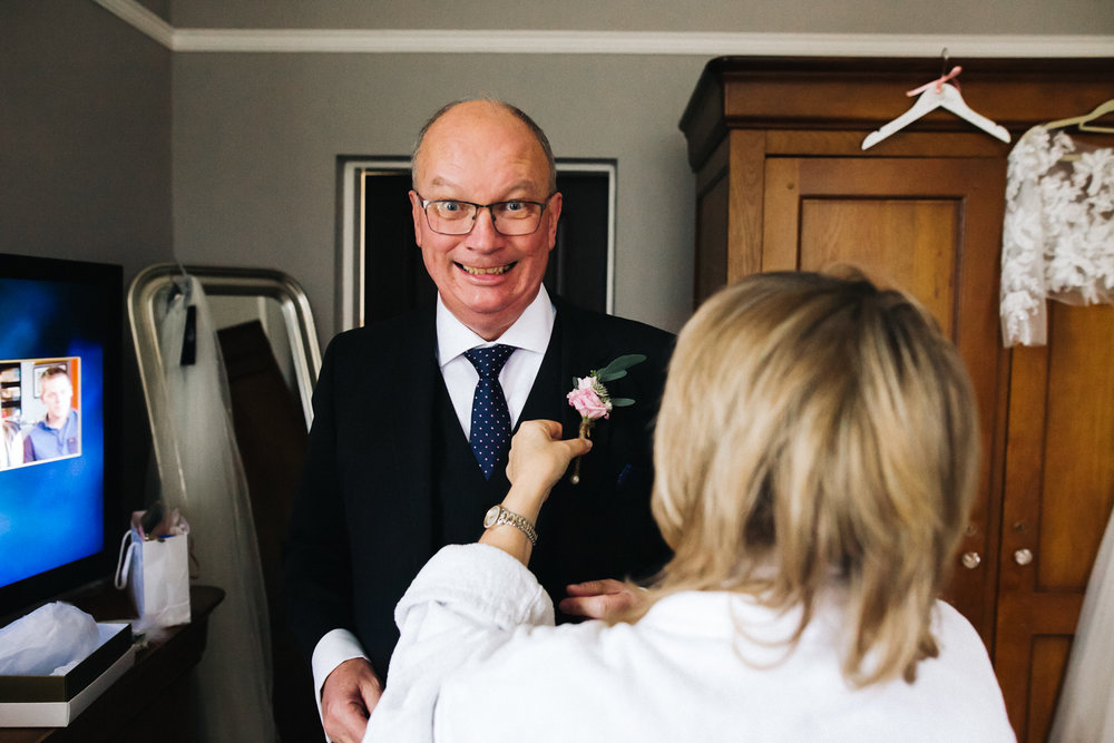 a father of the bride grins at the camera as his buttonhole is fitted. wedding at woodlands hotel in leeds. stop motion wedding films videos uk