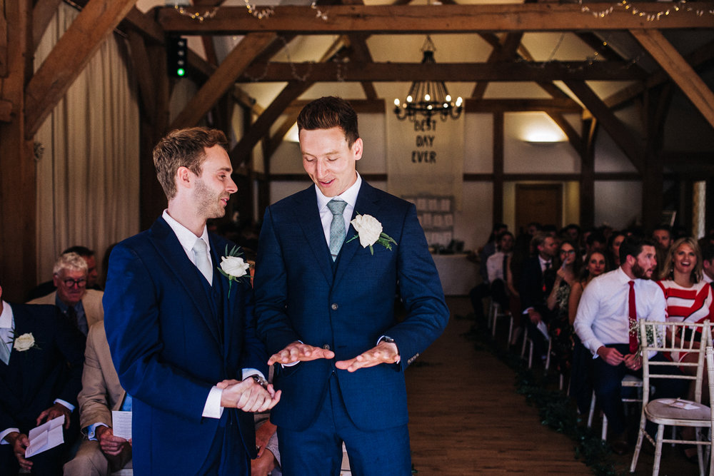 a groom looks at his shaking hands ahead of his wedding ceremony. sandhole oak barn cheshire wedding photographer. stop motion wedding films videos uk