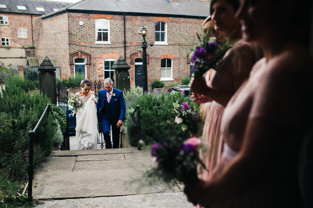 a bride walks up the church steps towards the church door with her father. merchant adventurers hall wedding york city centre. stop motion wedding films videos uk
