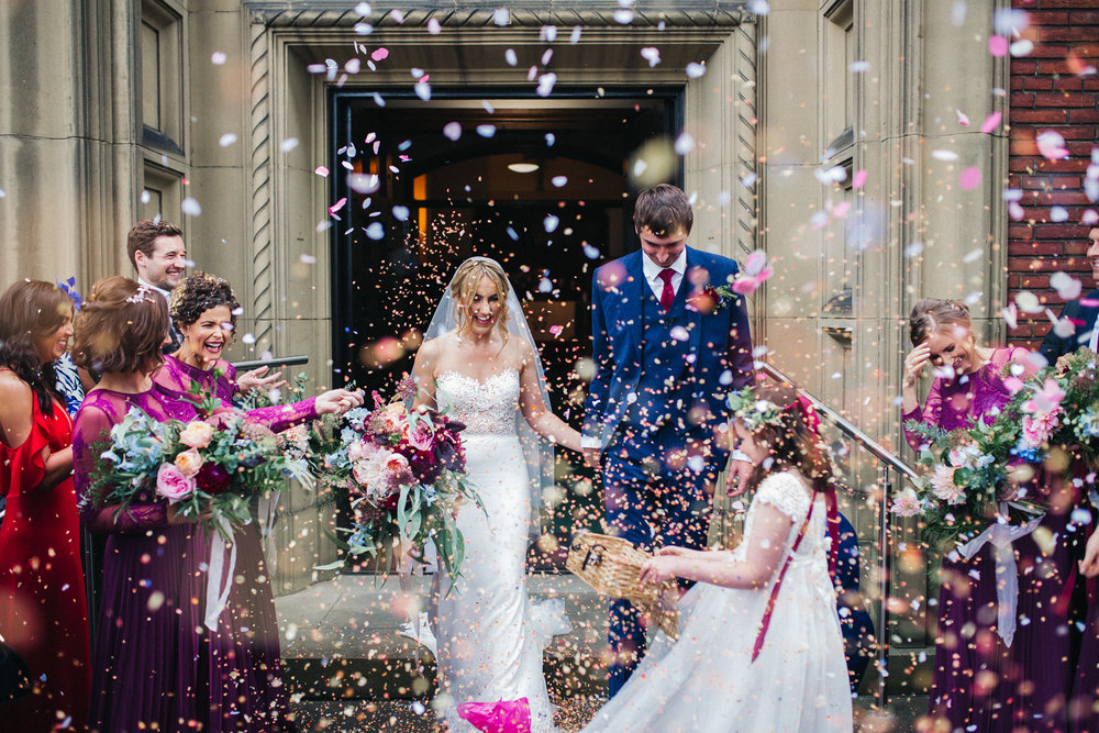 a man and woman walk out of church into a shower of confetti. ormesby hall wedding middlesbrough photographer. stop motion wedding films videos uk