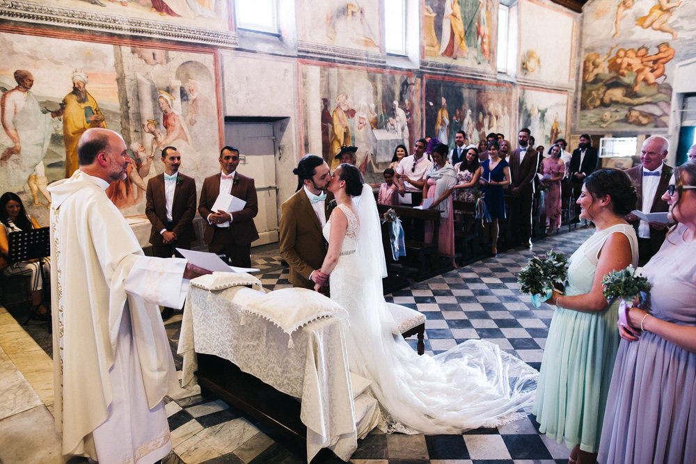 a bride and groom kiss in a heavily decorated italian church. destination wedding italy florence pisa chiavari. stop motion wedding films videos uk