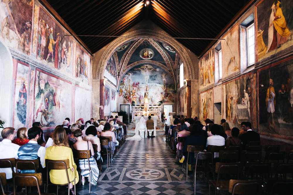 a bride and groom sit in an ornately painted italian church. destination wedding italy chiavari pisa florence. stop motion wedding films videos uk