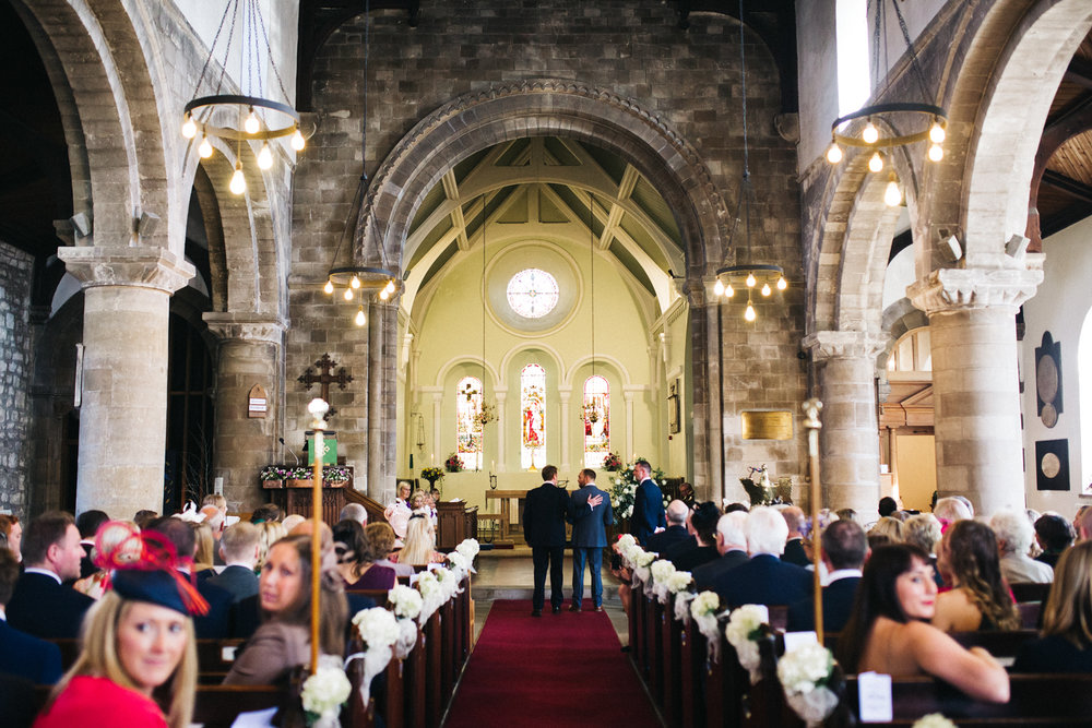 two men stand at the bottom of the aisle in church. talbot house wedding malton north yorkshire. stop motion wedding films videos uk