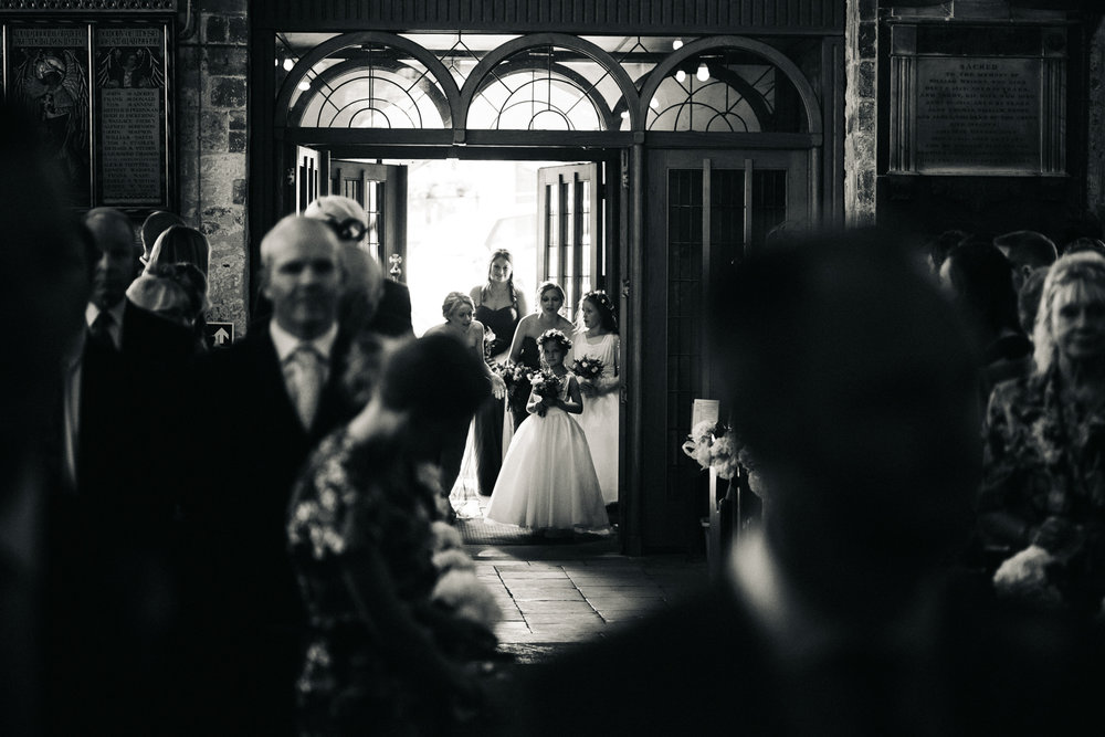 a black and white photo of a flower girl arriving at church. talboy house wedding malton near york, north yorkshire. stop motion wedding films videos uk