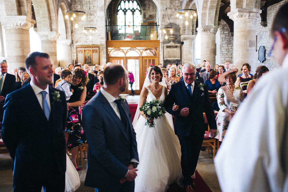a bride and groom smile at each other at the bottom of the aisle. talbot house wedding in malton near york. stop motion wedding films videos uk