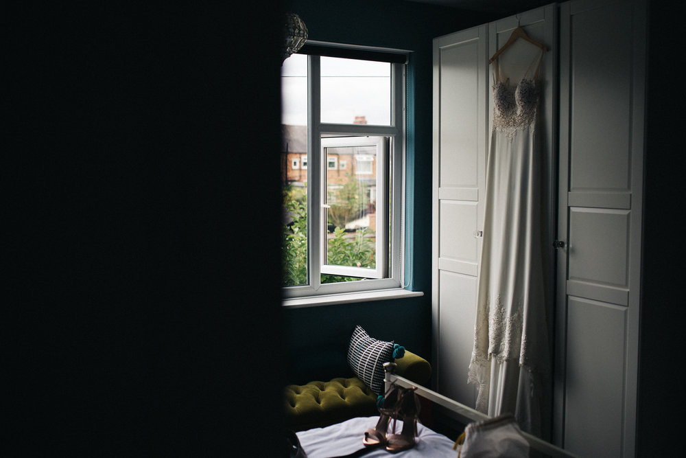 a dress hangs on a wardrobe by a window in the morning light. ormesby hall wedding middlesbrough. stop motion wedding films videos uk
