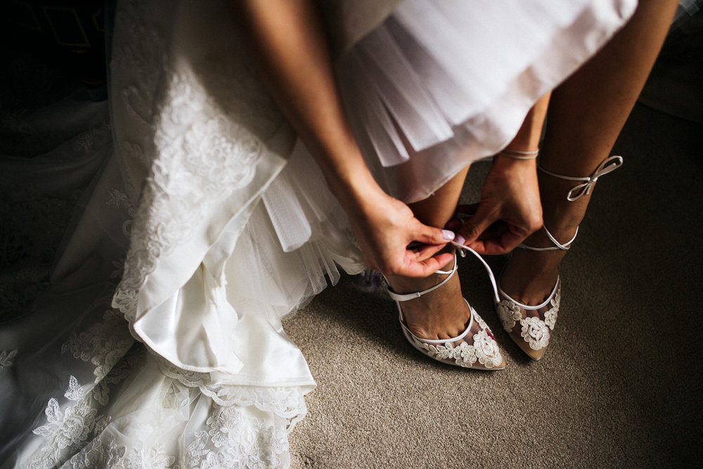 close up shot of bride doing up her shoes. dewsall courth wedding hereford photographer. stop motion wedding films videos uk
