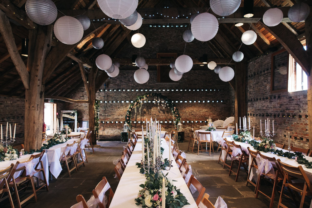 a barn filled with flowers, long tables and paper lanterns. tithe barn york north yorkshire. stop motion wedding films videos uk