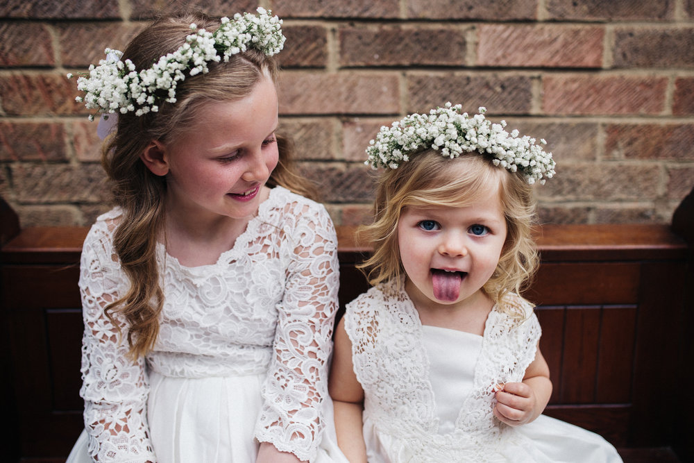 two flower girls, the youngest is sticking her tongue out at the camera